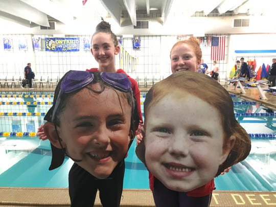 Shelby's record-setting duo of Reyna Hoffman and Rylie White have fun with their likenesses after Wednesday's Mid-Ohio Athletic Conference swim meet.