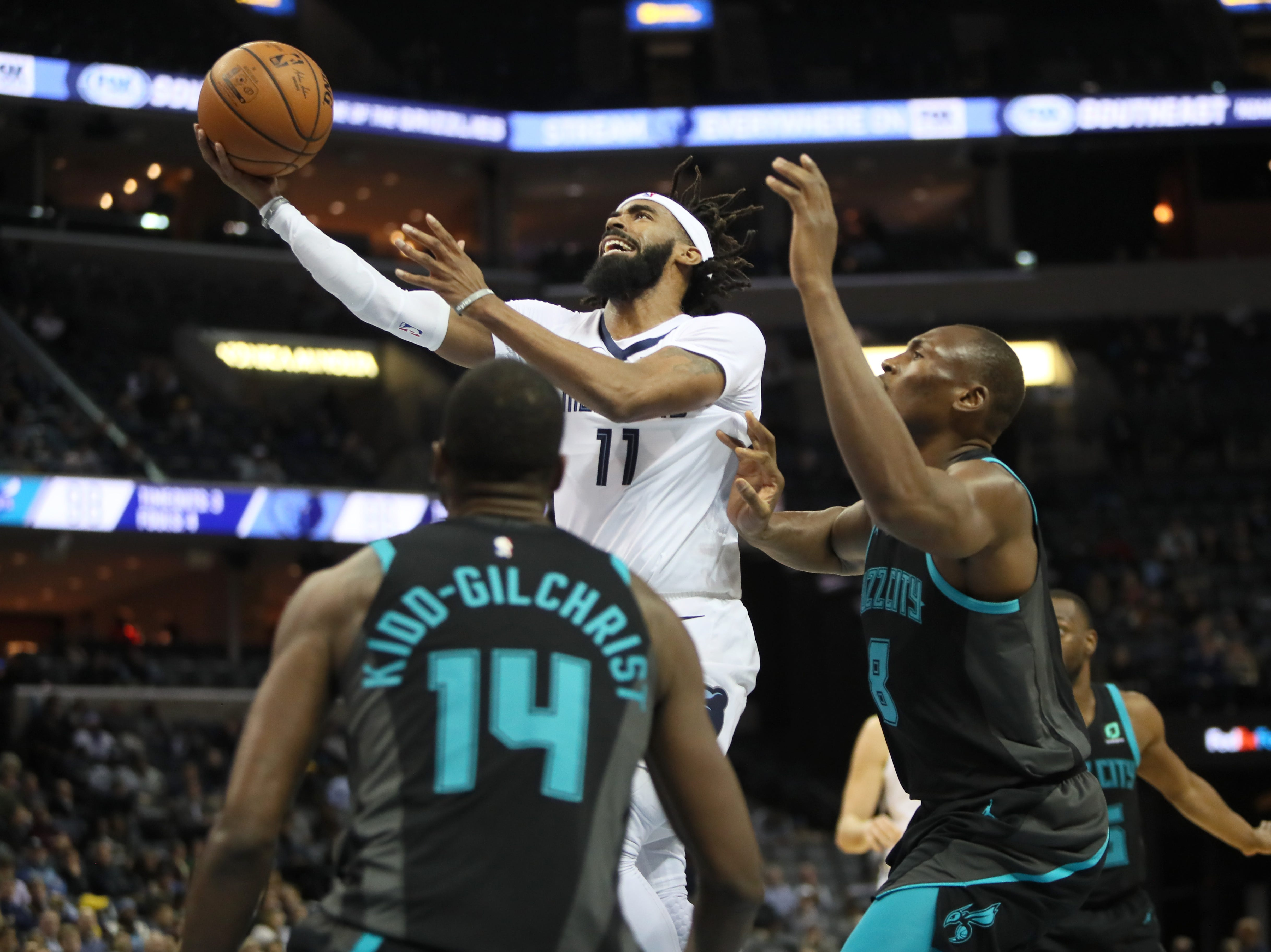 Memphis Grizzlies guard Mike Conley lays the ball up past Charlotte Hornets center Bismack Biyombo during their game at the FedExForum on Wednesday, Jan. 23, 2019.