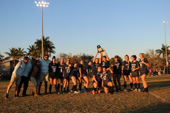 The Marco Island Academy girls soccer team holds up the trophy after winning the Paradise Coast Athletic Conference championship Monday with a 4-0 win over Donohue Academy.