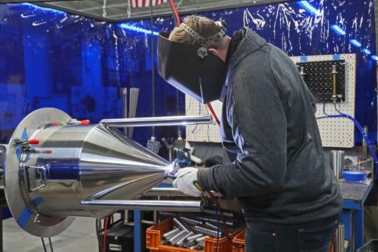 Jason Meyer welds a conical fermenter produced by Spike Brewing Equipment.