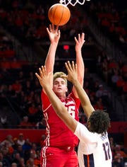 Badgers forward Nate Reuvers tosses home two of his career-high 22 points over Illinois center Adonis De La Rosa during the second half Wednesday night in Champaign, Ill.