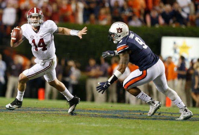 Auburn defensive end Byron Cowart (9) chases Alabama quarterback Jake Coker (14) in the Iron Bowl Saturday, Nov. 28, 2015, in Auburn, Ala.
