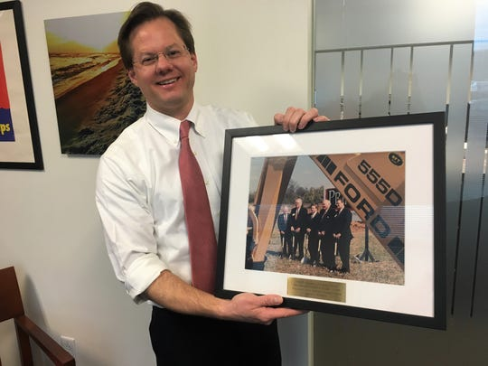 Williamson, Inc. CEO Matt Largen holds a framed photo from a 1994 groundbreaking ceremony for Primus Automotive Financial Services, one of the first company headquarters to relocate to the county.