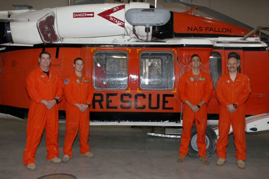 """The Longhorns Search and Rescue team from Naval Air Station Fallon that conducted a rescue in the Sierra Mountains stand by one of their three MH-60S """"Knighthawk"""" helicopters. From left to right are Lt. Cmdr. Joshua Haggard, crew chief Naval Aircrewman Helicopter 2nd Class Jacob Glende, Naval Aircrewman Helicopter 2nd Class Michael Dragan-Gosselin and mission commander Lt. Cary Lawson."""