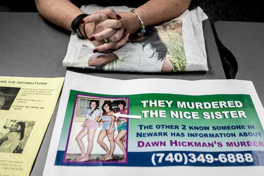 Michelle Laverty's hands rest on a T-shirt with her sisters picture on the front next to a copy of the billboard ad currently up in Newark, looking for answers to who murdered her sister 10 years ago.