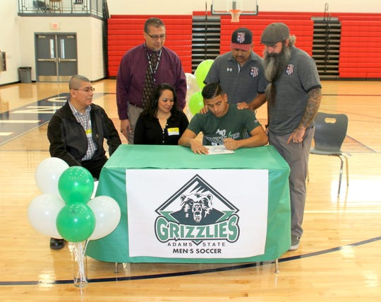 Deming High senior Paul Saucedo, seated at right, signs a letter of intent to play soccer at Adams State in Alamosa, CO. Seated with Paul are his parents Armando and Gloria Saucedo. Standing from left are DHS Athletic Director Bernie Chavez and DHS coaches Osvaldo Munoz and Jesse Kriegel.