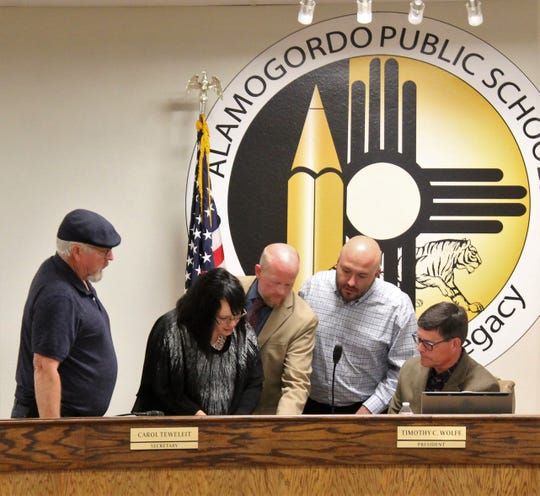 From left: APS Board member DAvid Weaver, APS Executive Assistant Lisa Patterson, APS Superintendent Jerrett Perry, K-12 Accounting Co-CEO Bryan Runyan and APS Board of Education President Timothy Wolfe review the K-12 Accounting contract with APS. APS hired K-12 Accounting to help with their finance issues including findings from the 2018 regular audit.