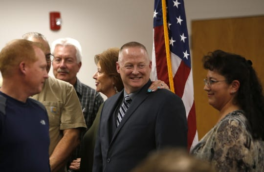 Newly hired Bloomfield Police Chief David Karst prepares to have his picture taken with city leaders Wednesday in Bloomfield.