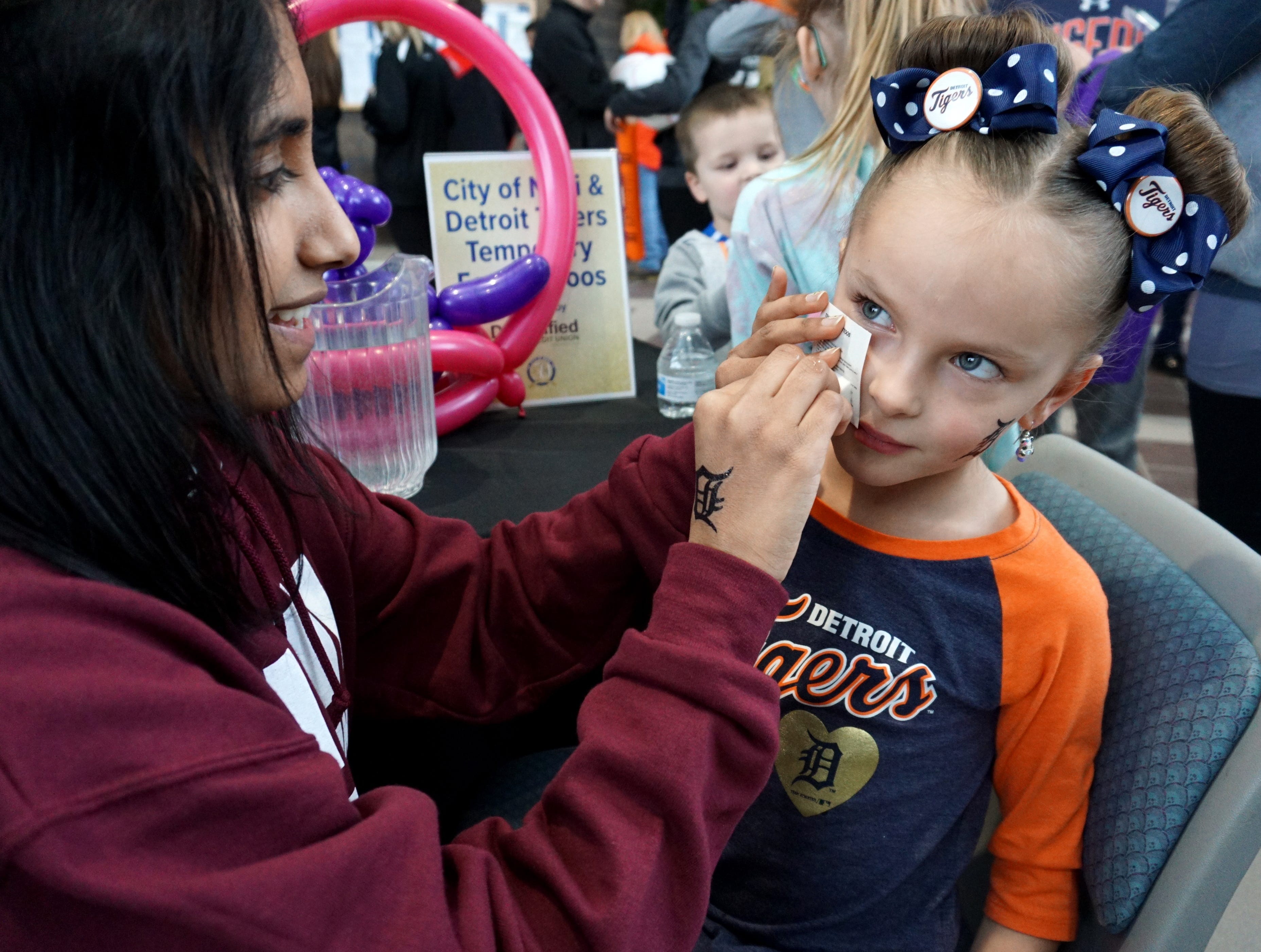 Sydney Vargo, 6, gets an olde English D stenciled to her cheek by Krishna Kiru during the Detroit Tigers' Winter Caravan visit to the city on Thursday.