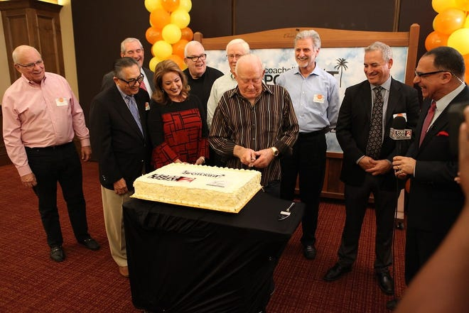 Ronald Auen, President of the H.N. and Frances C. Berger Foundation, cuts a cake to commemorate $3 million in grants to local nonprofit organizations through the Coachella Valley Spotlight. Celebrating with him are Don Perry, Francis Wong, Mike Stutz, Catharine Reed, Christopher McGuire, Darrell Burrage, Joe Glassett, Jerry Upham, and Patrick Evans.