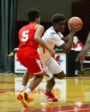 Damien King of Palm Springs tries to drive past Jared Wilson of Palm Desert. The Palm Springs varsity basketball team lost Wednesday's home conference game against Palm Desert by a score of 51-43.