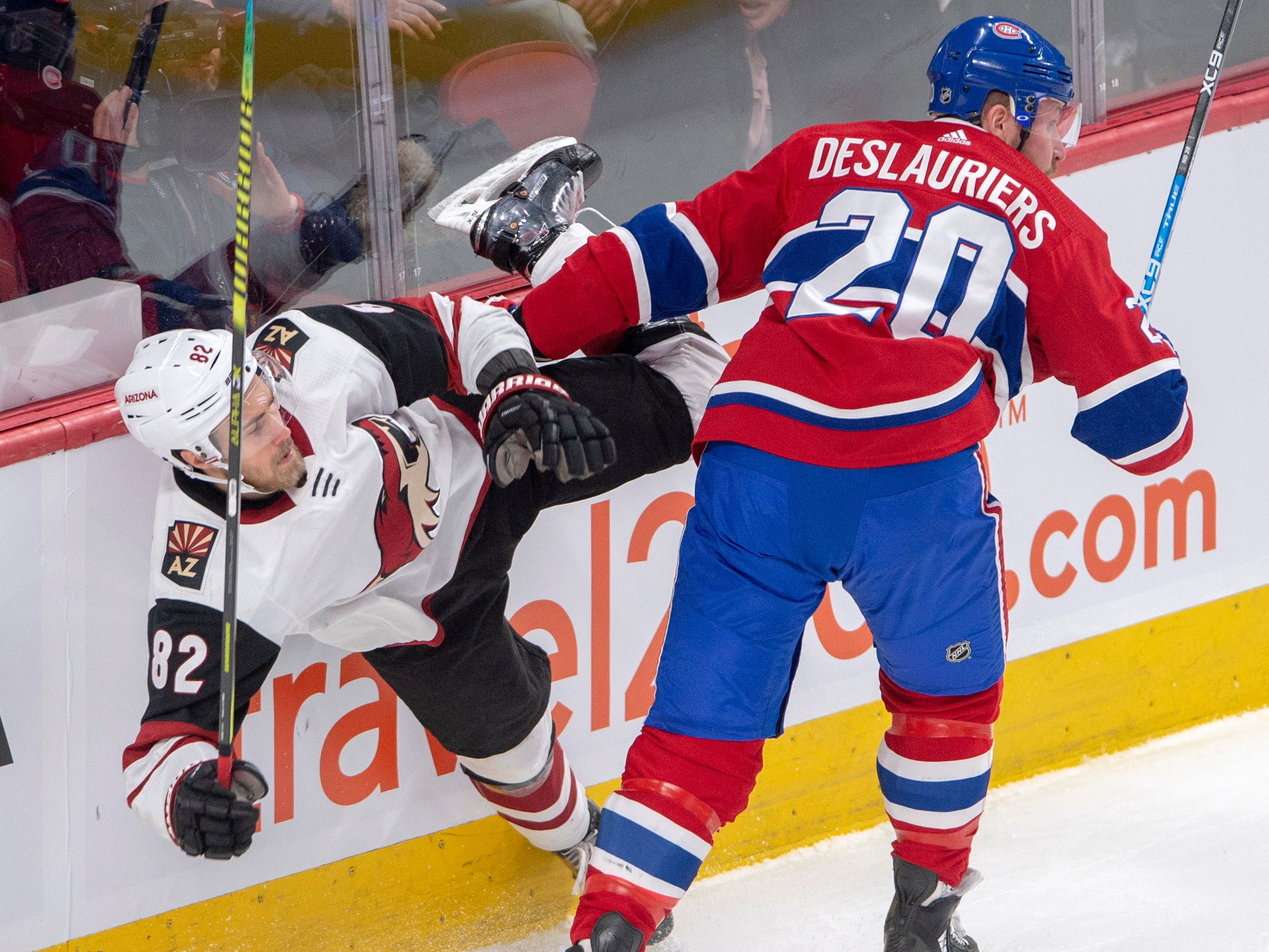 Arizona Coyotes defenseman Jordan Oesterle (82) is checked by Montreal Canadiens left wing Nicolas Deslauriers (20) during the first period of an NHL hockey game Wednesday, Jan. 23, 2019, in Montreal.