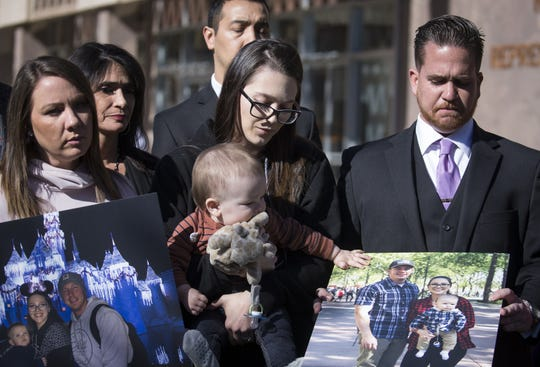Deanna Townsend, widow of Officer Clayton Townsend (center) holds her son, Brixton, during a press conference introducing  a bill to ban handheld phone use while driving on Jan. 24, 2019, on Arizona House Lawn. Officer Townsend was struck and killed by a distracted driver.