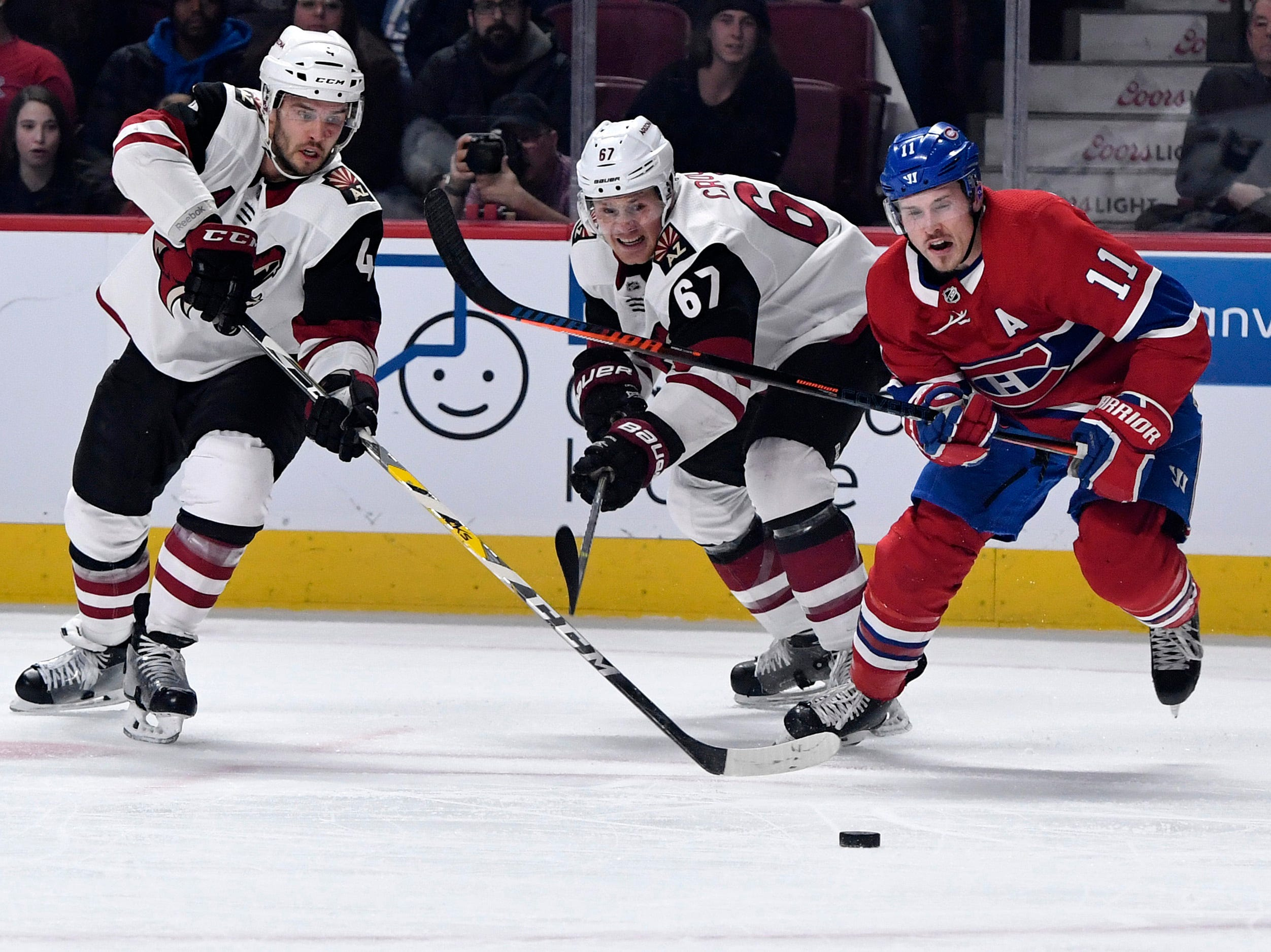 Jan 23, 2019; Montreal, Quebec, CAN; Montreal Canadiens forward Brendan Gallagher (11) chases the puck ahead of Arizona Coyotes defenseman Niklas Hjalmarsson (4) and teammate Lawson Crouse (67) during the first period at the Bell Centre. Mandatory Credit: Eric Bolte-USA TODAY Sports