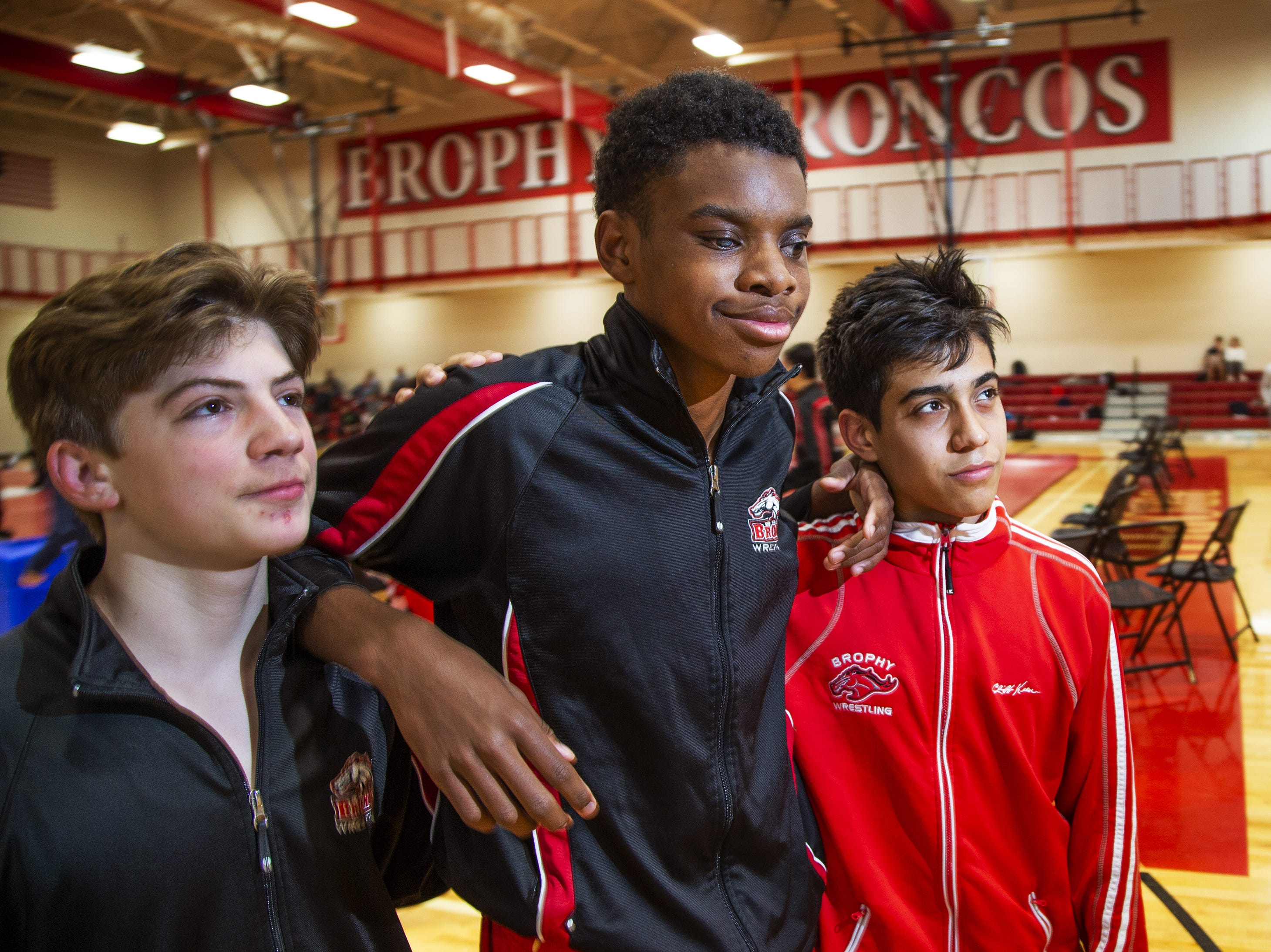 Adonis Watt, middle, is a blind wrestler for Brophy College Preparatory high school in Phoenix.  He hangs out with his teammates and friends, Grant Buccino, left, and Joseph Martinez, right, before his match at Brophy, Wednesday, January 23, 2019.