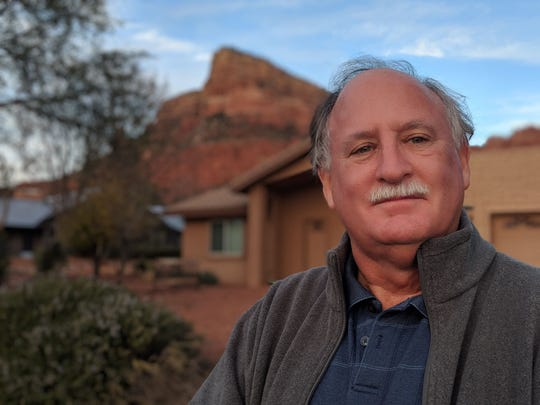 Sedona City Councilmember Scott Jablow stands in front of a home being operated as a short-term rental. City officials and residents say the law has exacerbated a growing problem of unavailable housing that could have far-reaching consequences for their city.