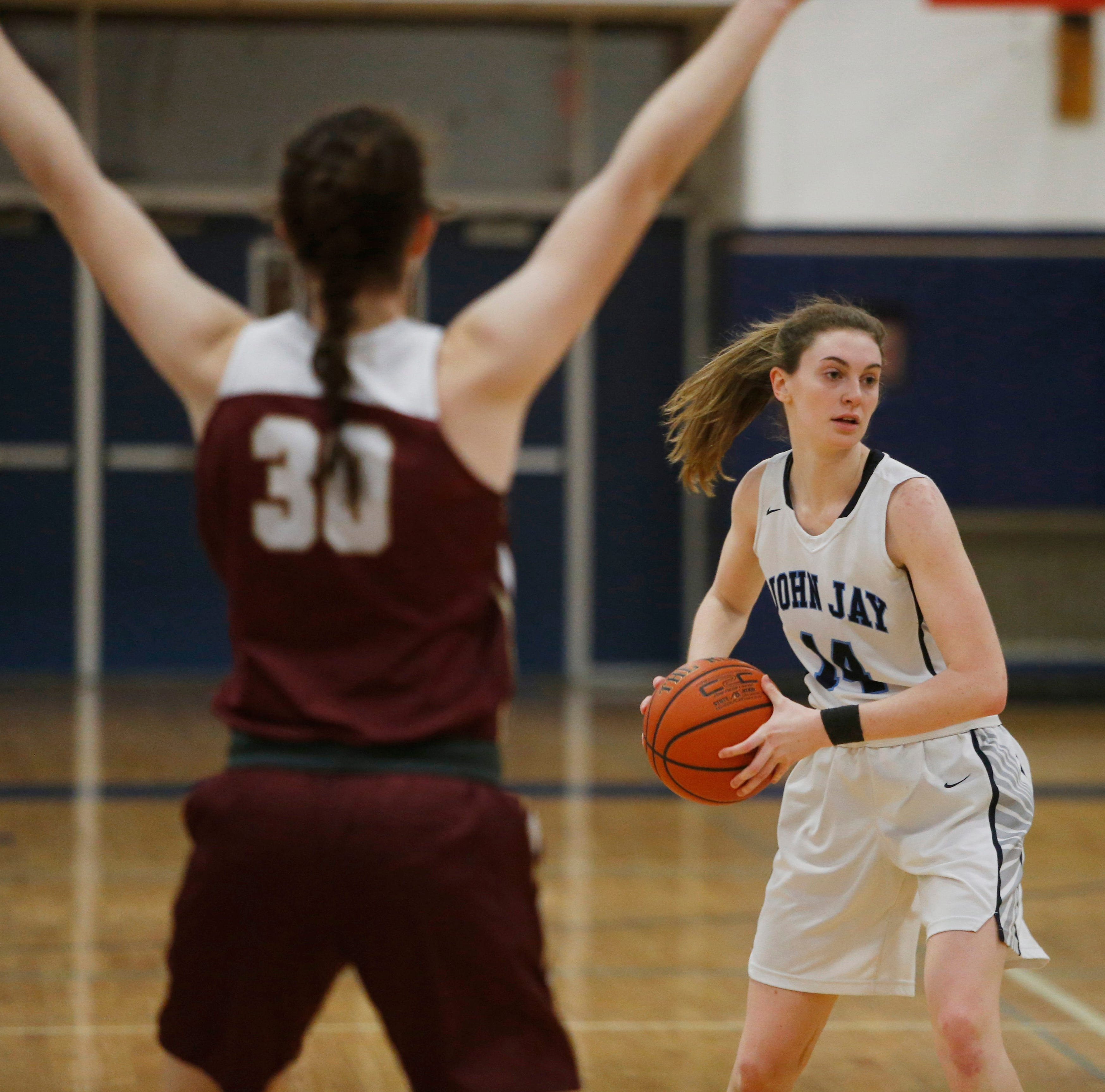 John Jay's Haley Karst looks to pass the ball as Arlington's Emily Mahon covers her during Wednesday's game in Wiccopee on January 23, 2019.