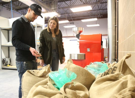 Jesse Barr and Emily Jordan of Ready Coffee inspect green coffee beans before roasting at the company's headquarters in Wappingers Falls on January 24, 2019.