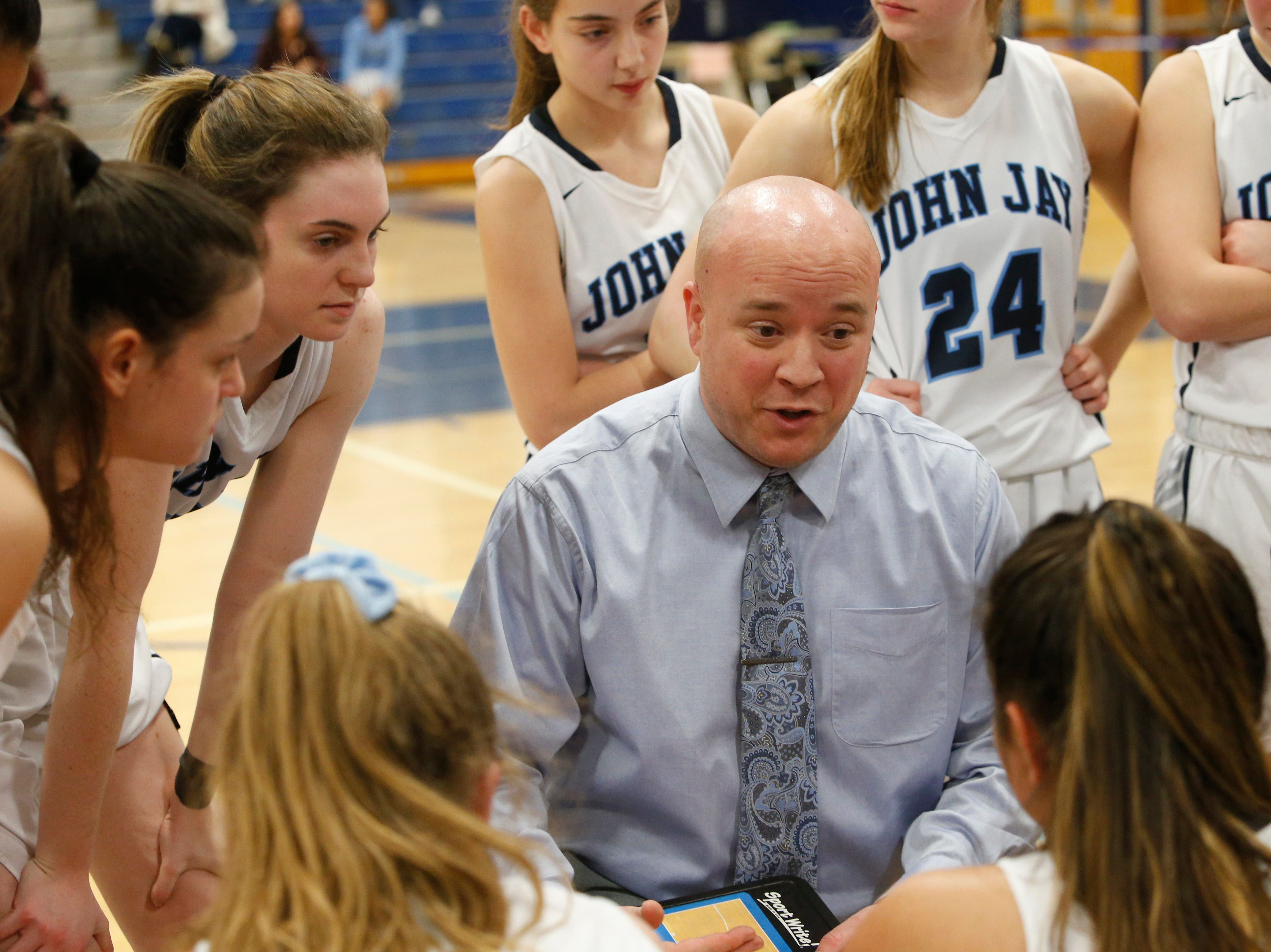 John Jay girls basketball coach Larry Brooks discusses strategy with his team in a timeout during Wednesday's game.