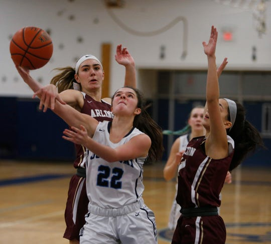 John Jay's Alyssa Caswell fights for a layup as Arlington's Devon Schmitt, left, defends during Wednesday's game in Wiccopee on January 23, 2019.