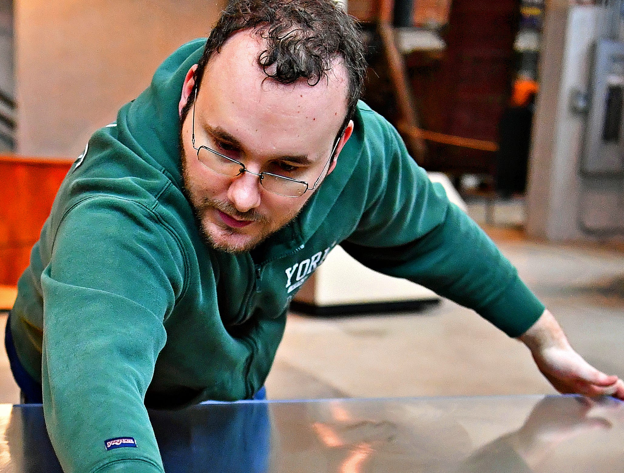 Registrar Bryan Bailey shines the glass on display cases as York County History Center staff spend the day cleaning the Agriculture & Industrial Museum in York City, Thursday, Jan. 24, 2019. The museum is one of five under the History Center umbrella, all of which are closed Jan. 22-25 for their annual spring cleaning. Dawn J. Sagert photo