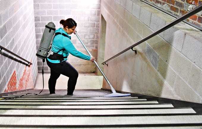 """York County History Center's Director of Collections Rachel Warner vacuums the stairwell at the Agriculture & Industrial Museum in York City, Thursday, Jan. 24, 2019. The museum is one of five under the History Center umbrella, all of which are closed Jan. 22-25 for their annual, """"Spring Cleaning,"""" according to their facebook page. Dawn J. Sagert photo"""