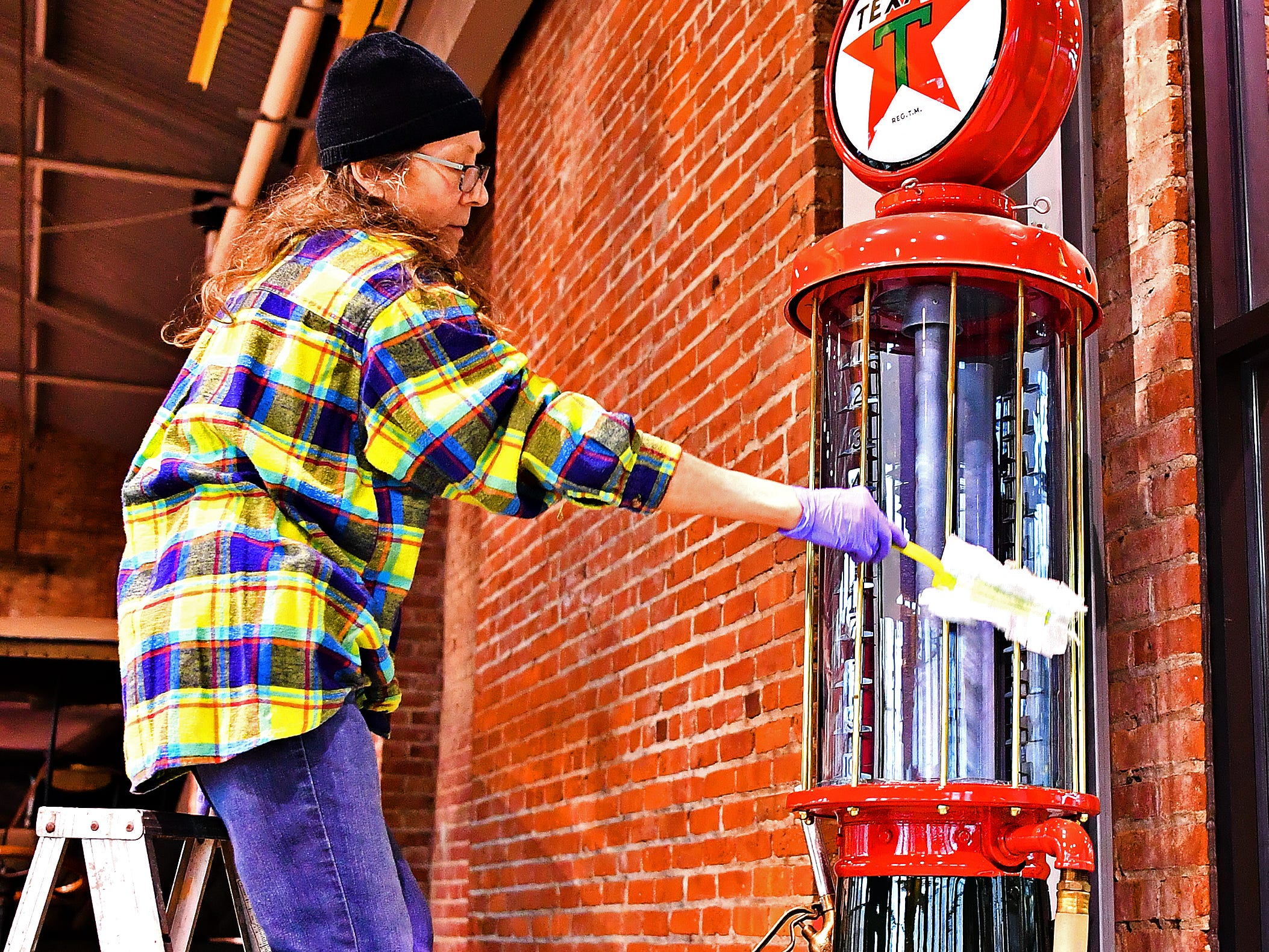 York County History Center Lobby Coordinator Kate Redshaw stands on a ladder to thoroughly dust a tall Texaco gas pump as she and other staff spend the day cleaning the Agriculture & Industrial Museum in York City, Thursday, Jan. 24, 2019. The museum is one of five under the History Center umbrella, all of which are closed Jan. 22-25 for their annual spring cleaning. Dawn J. Sagert photo