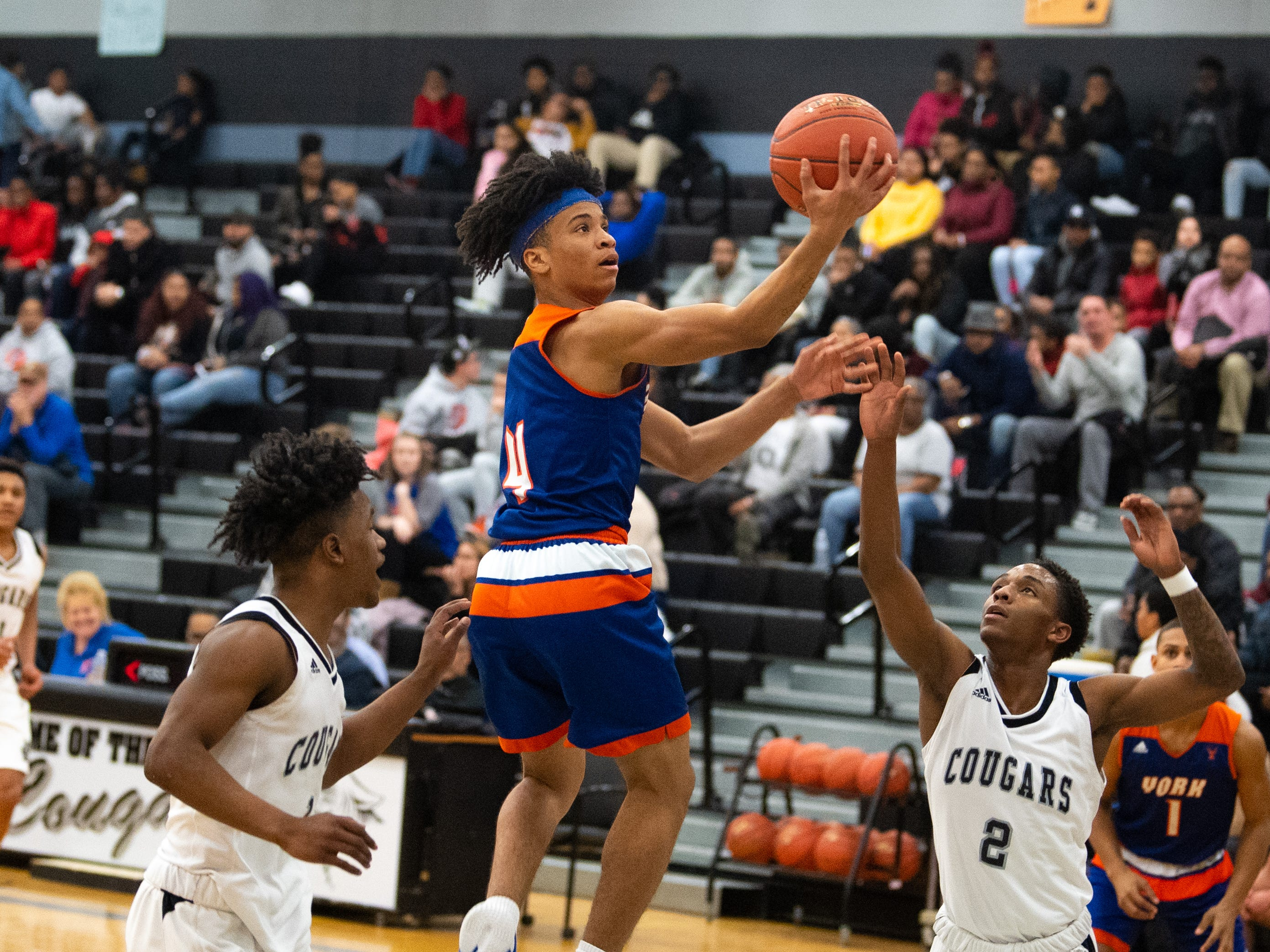Jaevon Woodyard (4) sails to the basket during the boys' basketball game between Harrisburg High and York High, Wednesday, January 23, 2019. The Cougars defeated the Bearcats 69-65.