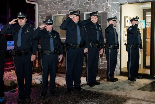 Law enforcement officers salute Tazer as he walks into Valley Green Veterinary Hospital on Wednesday. Dozens of police officers and K-9 units showed support for Tazer and handler, Sgt. Chris Martinez of Newberry Township.