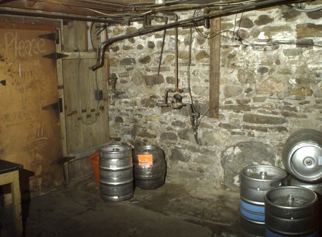 The basement of the Reunion Inn in Irondequoit, where Steve Sahs locked himself in the freezer on the left. The big stone by the kegs is thought to possibly be a tomb, but no one knows for sure.