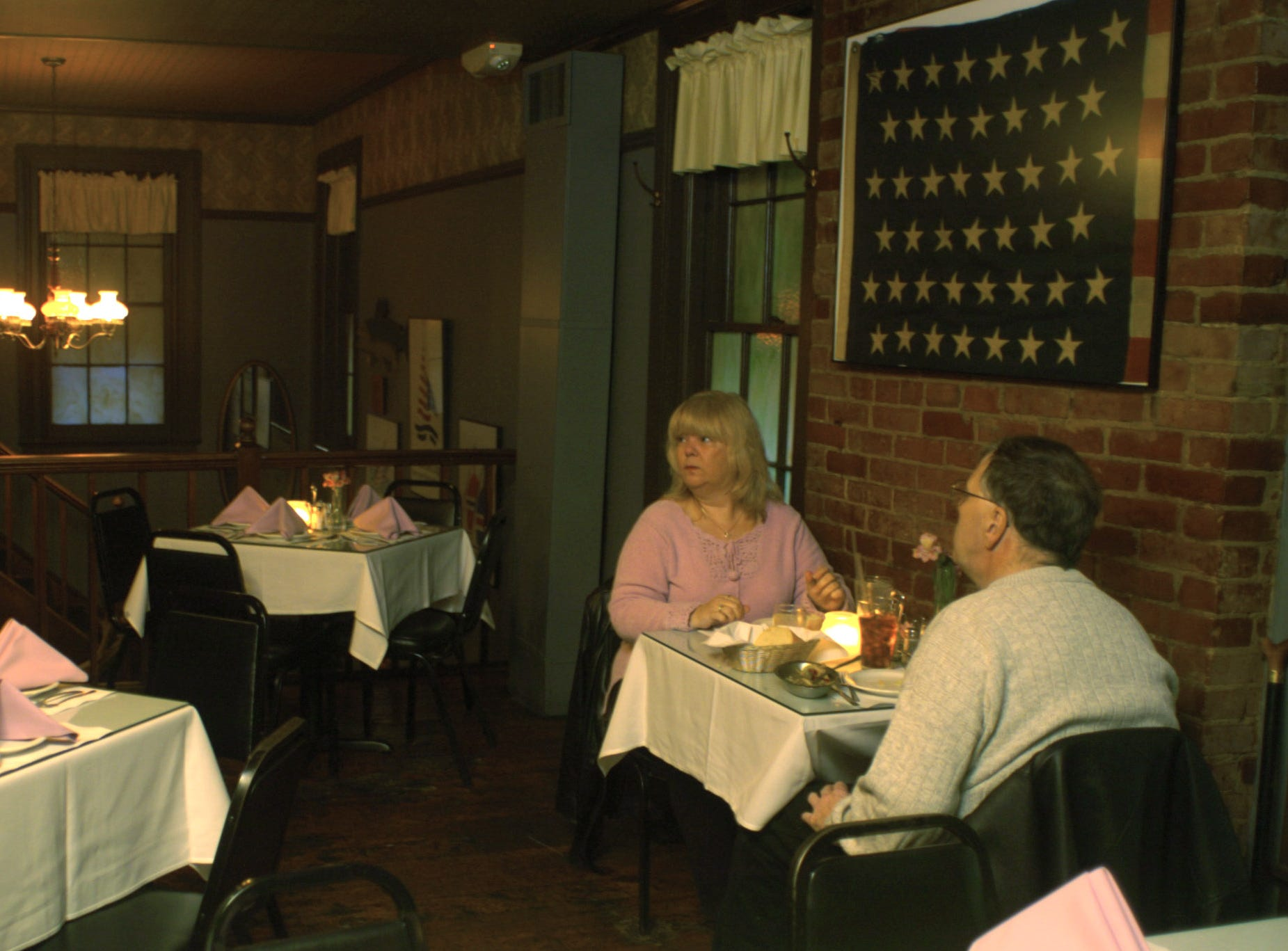 Barbara McColl and Robert Moss eat underneath the 1895 45-star flag at the Reunion Inn in Seabreeze in 2006.