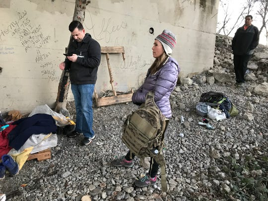 Dominic De Lello, Shannon Hunt and Daren Fisher speak with a man and a woman who'd slept under the Market Street Bridge. Written on the wall: 'Not homeless *Home Free*'