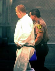 Frank Milligan (left) is escorted by a Marion County Deputy after being sentenced to 30 years in prison for the abduction and neck slashing of a Dallas boy in July 2000.