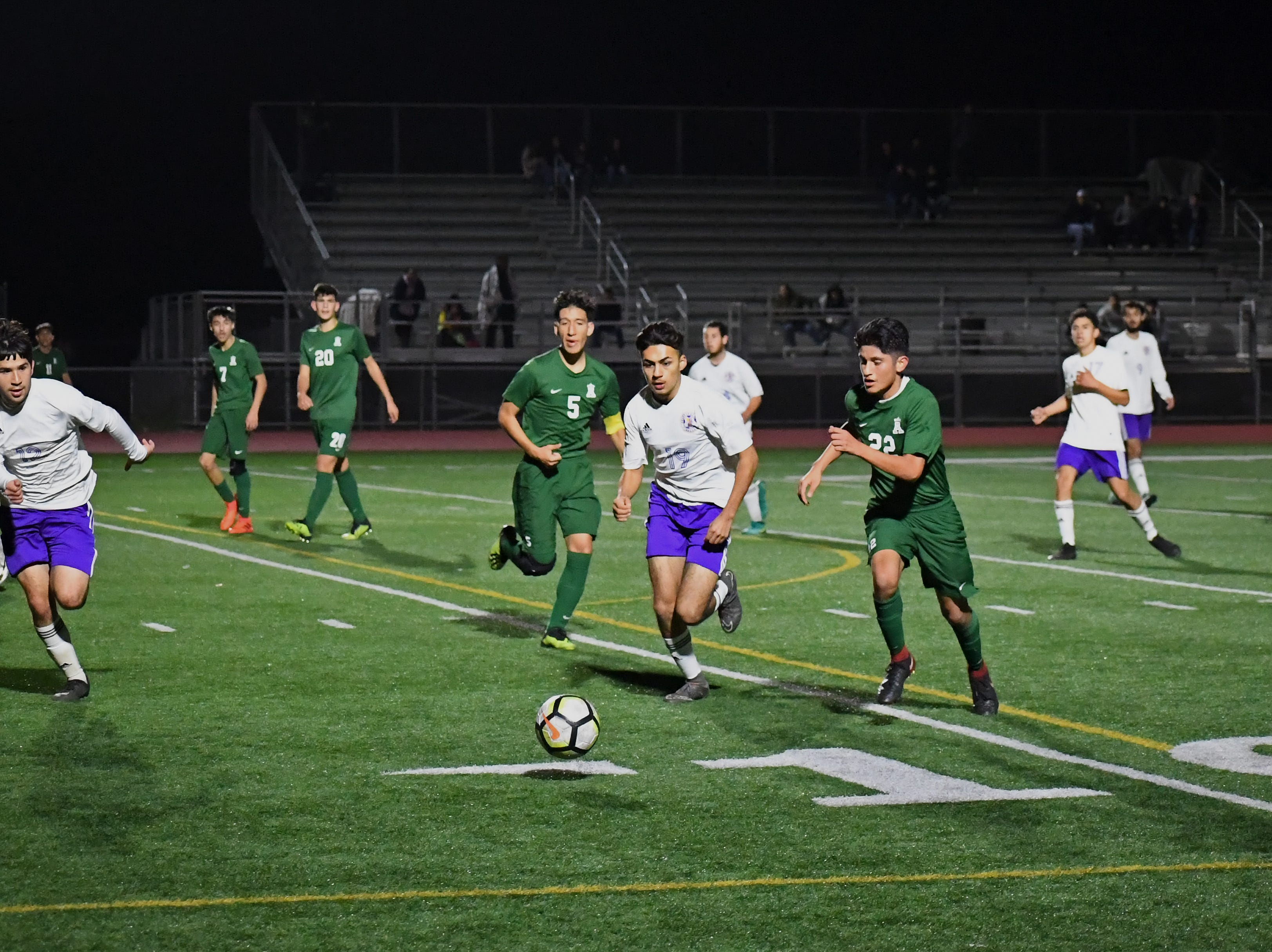 Alisal defender Joel Garcia (22) sprints ahead of multiple Soledad defenders to gain possession.