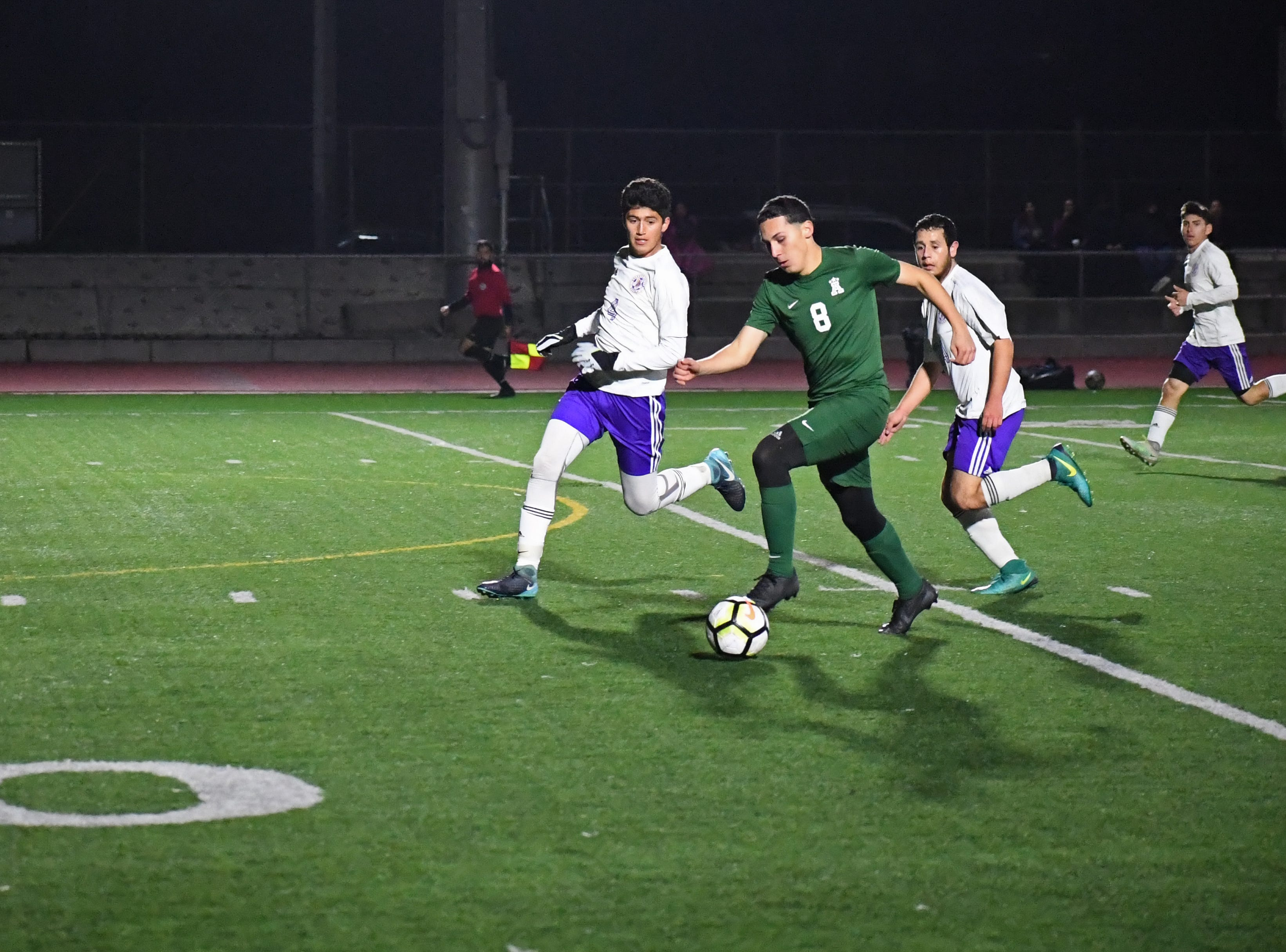 Alisal striker Armando Alvarez (8) sprints past two defenders.