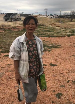 """Unja Baliko stops for a moment near the Red Arroyo in San Angelo while making her daily rounds picking up trash and keeping her neighborhood """"bright."""""""