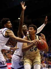 LAWRENCE, KANSAS - DECEMBER 04:  Keve Aluma #24 of the Wofford Terriers controls the ball as Dedric Lawson #1 and Marcus Garrett #0 of the Kansas Jayhawks defend during the game at Allen Fieldhouse on December 04, 2018 in Lawrence, Kansas. (Photo by Jamie Squire/Getty Images)