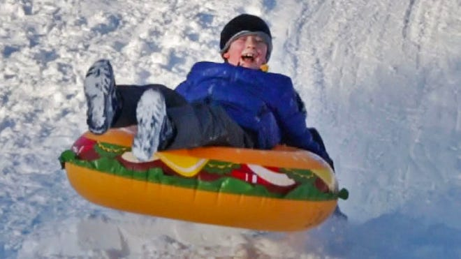 A boy reacts to hitting a bump on his way down Vollrath Bowl, Wednesday, January 23, 2019, in Sheboygan, Wis. Fresh snow has made sledding a popular activity with people of all ages.