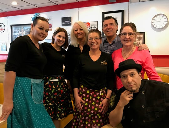 Christina Latifi and Harry Ljatifovski with the staff at Harry's Diner. Latifi says she gets the girls custom made poodle skirts to blend in with the 50s theme.