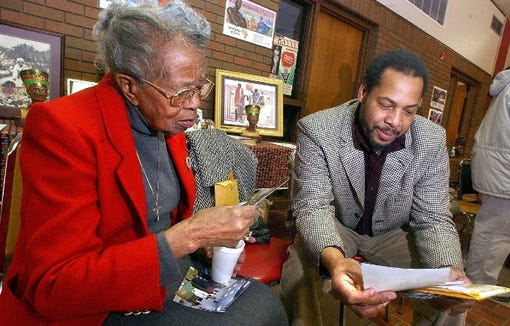 Emma Armstrong looks over old photographs with NAACP chapter president Daniel Brooks in 2004 during the 60th anniversary celebration of the chapter in Sioux Falls.
