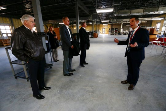 Nixa High School principal Mark McGehee walks school board members through an unfinished section of the third floor. The area will be used as classroom space if the bond issue is approved.