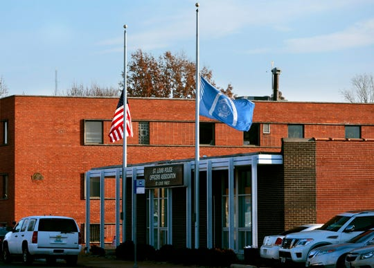 Flags fly at half-staff in front of the St. Louis Police Officers Association on Thursday, Jan. 24, 2019, following the shooting death of a police officer.  Authorities say a St. Louis police officer has accidentally shot and killed another officer. The shooting happened around 1 a.m. Thursday when two on-duty male officers went to one of their homes during their shift. Police Chief John Hayden said during a news conference that a 24-year-old off-duty officer was shot in the chest when she stopped by the home.  (Robert Cohen/St. Louis Post-Dispatch via AP)