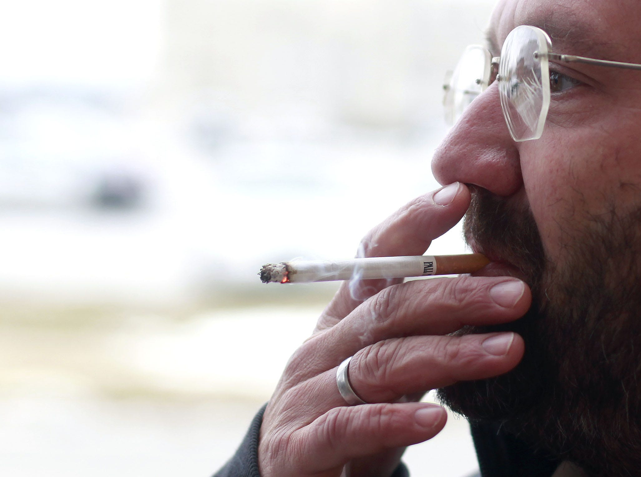 In this 2014 file photo, then-homless Joe Moreira smokes a cigarette while outside of the Veterans Coming Home center. Moreira died Sunday