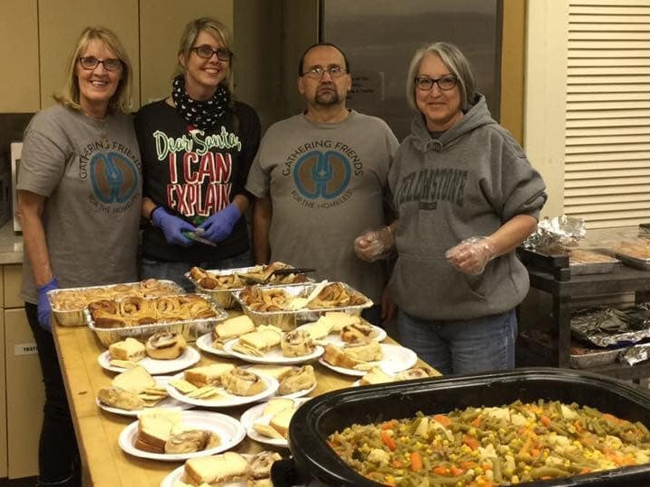 Joey Moreira poses with Gathering Friends volunteers before serving a meal to homeless people at Grace United Methodist Church.