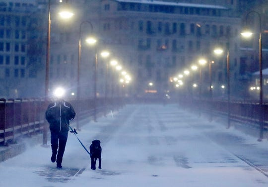 A runner and his dog brave frigid conditions while making their way east across the Stone Arch Bridge Thursday, Jan. 24, in Minneapolis.   The National Weather Service issued a wind chill advisory overnight Thursday for Wisconsin, Minnesota, the Dakotas and several other states where temperatures were expected to plunge to 30 below with the wind as a factor.