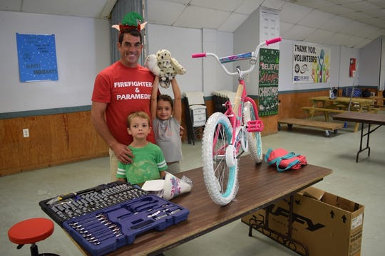 Clint Bradley, with son Hudson, and daughter Clara, volunteered to assemble bicycles with the Martin County Paramedics & Professional Firefighters for the White Doves Holiday Project.