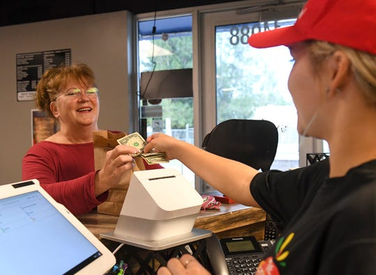 Susan Gibbs Thomas (left), Mayor of the Village of Indiantown, picks up her lunch order from Mackenzie Smith at The Fresh Stop restaurant at 12988 SW Monroe Avenue on Thursday, Jan. 24, 2019, in Indiantown.
