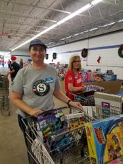 RSVP volunteer Sharon Leary assists families as they select presents for their children during United Way of Martin County's White Doves Holiday Project.