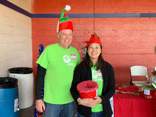 Ron Hix and Diane Diane Nguyen, volunteers from Florida Power & Light Co., volunteer at the White Doves Holiday Project.