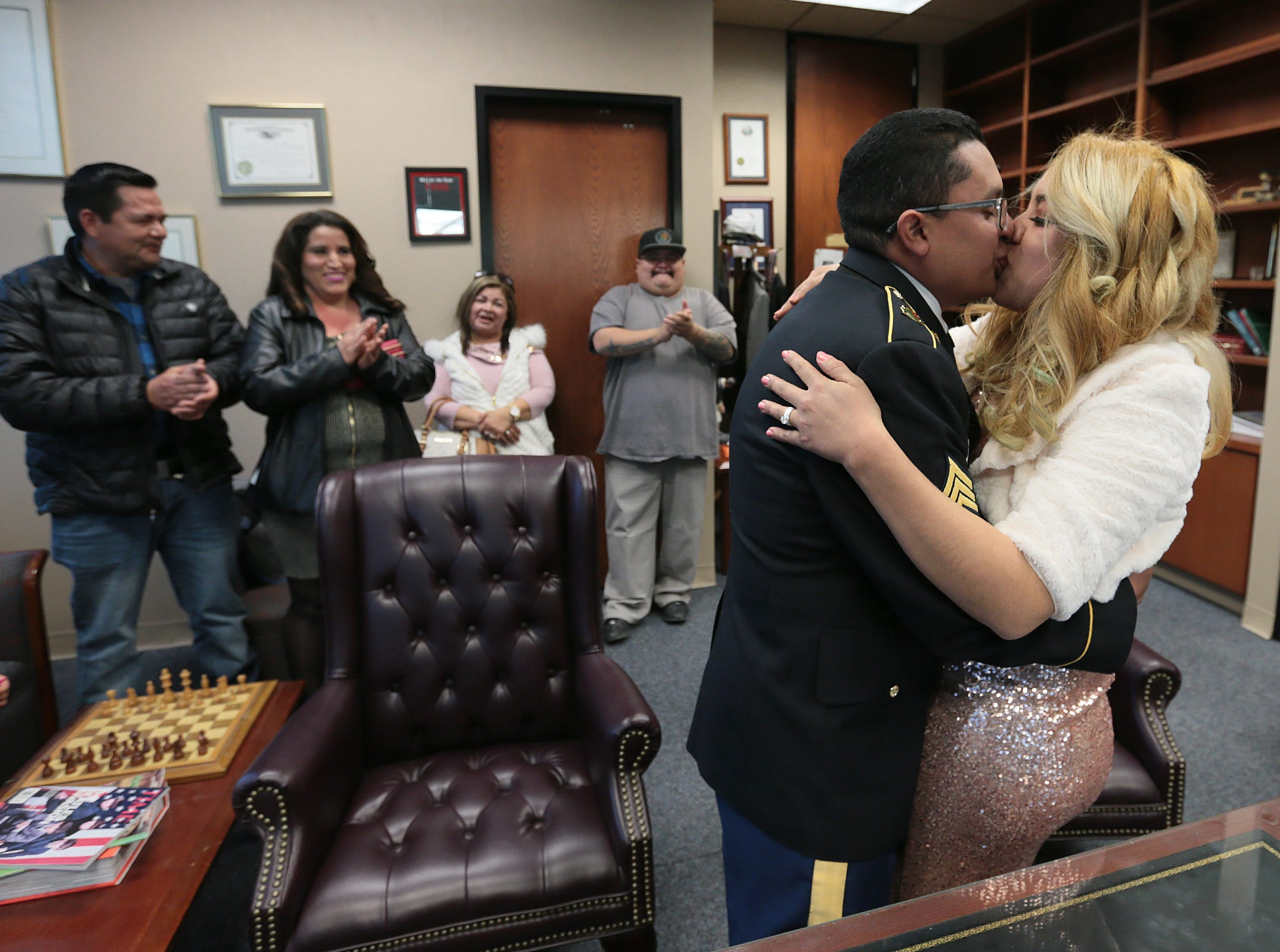 Randy Juarez and Carla Perez kiss Tuesday as they celebrate their marriage by Judge Patrick Garcia of the 384th District Court. Their family members applaud in the background.